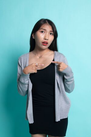 Young Asian woman point at herself ask why me on cyan background. Stock fotó