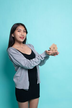 Happy young asian woman with house model on cyan background. Stock fotó - 137879688