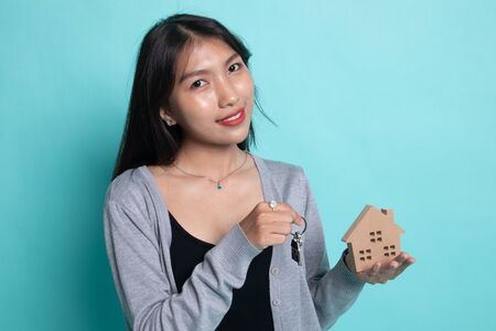 Happy young asian woman with house model and key on cyan background.