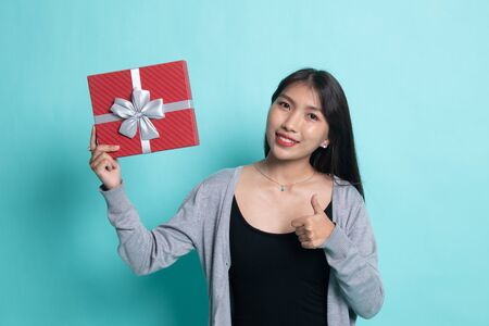 Young Asian woman thumbs up with a gift box on cyan background.