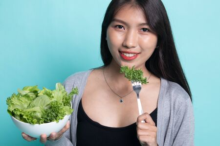 Healthy Asian woman with salad on cyan background. Stock Photo