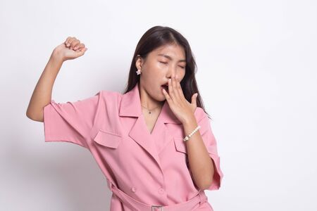 Sleepy young Asian woman yawn on white background.
