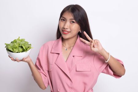 Healthy Asian woman show victory sign with salad on white background. Stock Photo