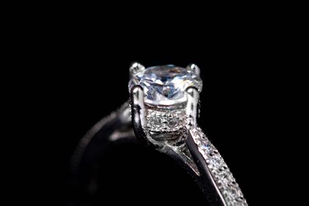 Close up of diamond silver ring on black background