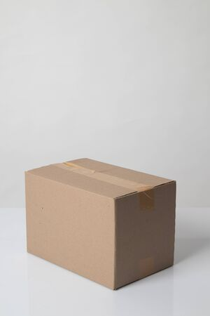 Closed cardboard box taped up ready to delivery on white background