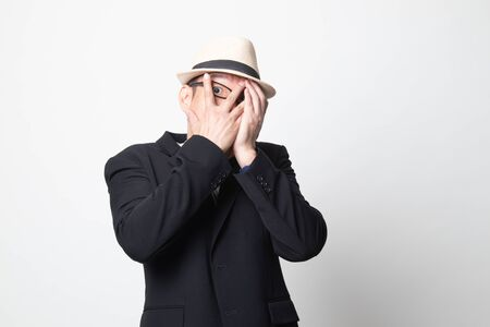 adult asian man peeking through fingers on white background