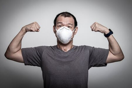 Strong Asian man wearing N95 mask to prevent flu virus and PM2.5 dust air pollution on white background