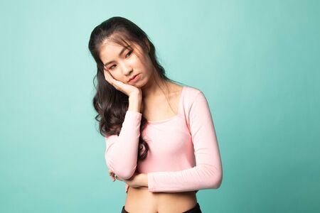 Beautiful young Asian woman get bored on cyan background