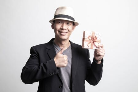 Adult Asian man thumbs up with a gift box on white background