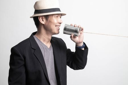 Adult Asian man with tin can phone on white background Foto de archivo