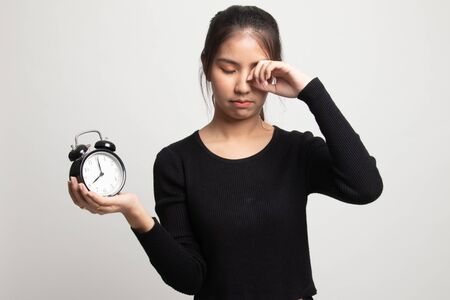 Sleepy young Asian woman with a clock in the morning on white background 版權商用圖片 - 142674444