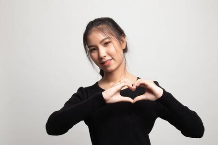Young Asian woman show heart hand sign on white background 版權商用圖片
