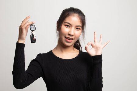 Cute asian girl showing home residence keys on white background 版權商用圖片 - 142674448