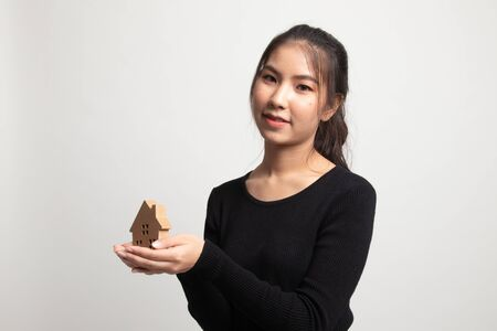 Happy young asian woman with house model on white background
