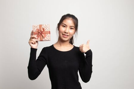 Young Asian woman thumbs up with a gift box on white background