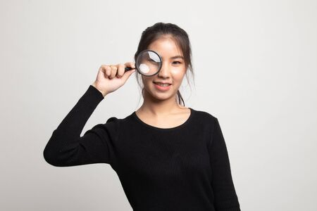 Young Asian woman with a magnifying glass on white background