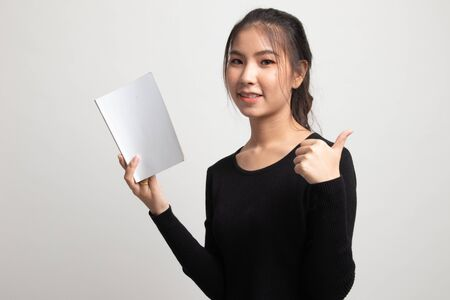 Young Asian woman thumbs up with a book on white background 版權商用圖片 - 142674457