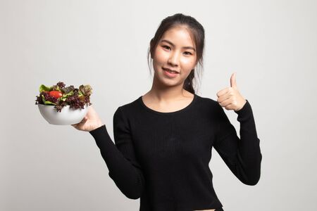 Healthy Asian woman thumbs up with salad on white background 版權商用圖片
