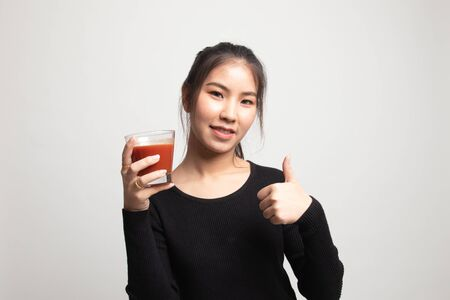 Young Asian woman thumbs up with tomato juice on white background