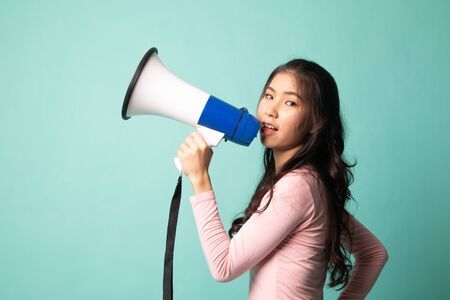 Beautiful young Asian woman announce with megaphone on cyan background
