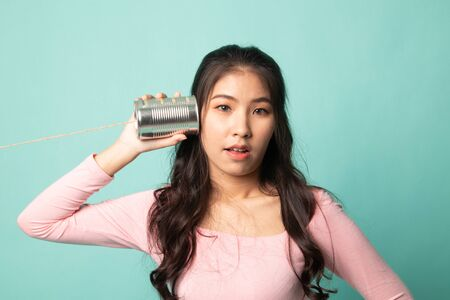 Surprised young Asian woman with tin can phone on cyan background