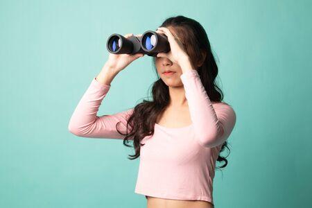 Young Asian woman with binoculars on cyan background 版權商用圖片 - 142674604