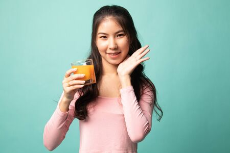 Happy Young Asian woman drink orange juice on cyan background