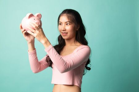 Young Asian woman with a pig coin bank on cyan background