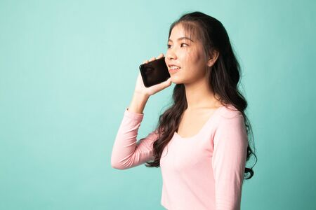 Young Asian woman talking with mobile phone on cyan background 版權商用圖片 - 142674607
