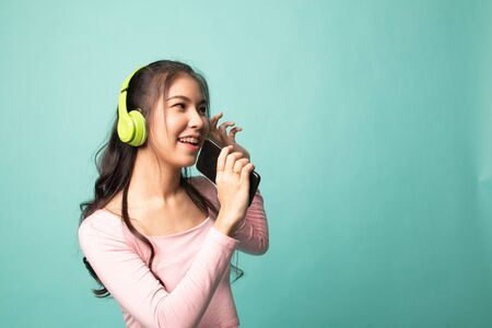 Pretty asian girl listening music with her headphones on cyan background 版權商用圖片