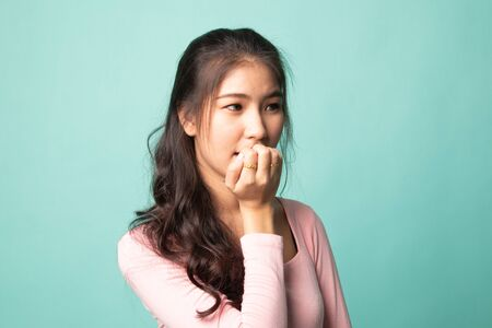 Unsure hesitant nervous young asian  woman biting her fingernails on cyan background 版權商用圖片