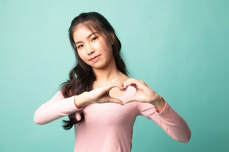 Young Asian woman show heart hand sign on cyan background