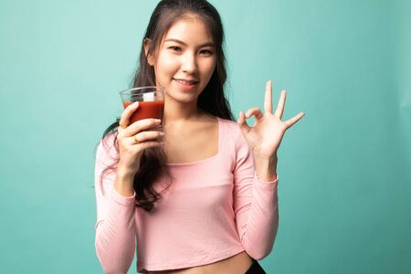 Young Asian woman show OK with tomato juice on cyan background