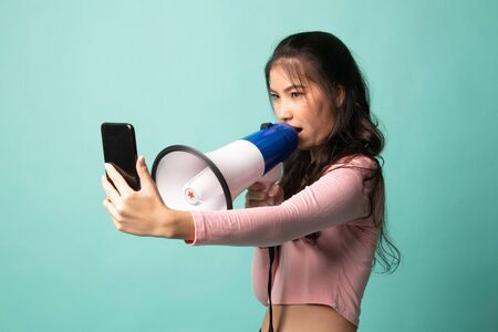 Angry  young Asian woman shout with megaphone to mobile phone on cyan background 版權商用圖片 - 142674619