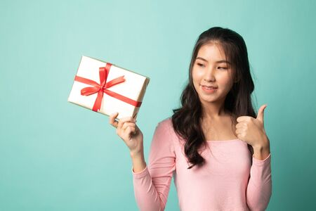 Young Asian woman thumbs up with a gift box on cyan background