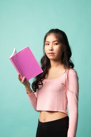 Young Asian woman read a book on cyan background 版權商用圖片 - 142674621