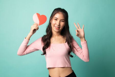 Asian woman show OK with red heart on cyan background 版權商用圖片 - 142674623
