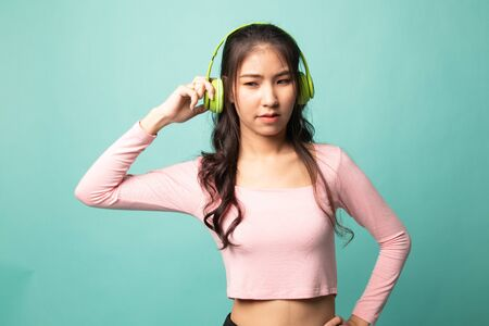 Too loud.  portrait of  young asian woman  holding  headphones and making unhappy face on cyan background
