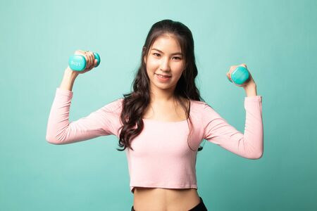 Healthy Asian woman with dumbbells on cyan background