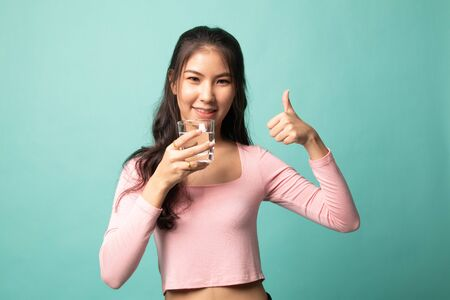 Young Asian woman thumbs up with a glass of drinking water on cyan background