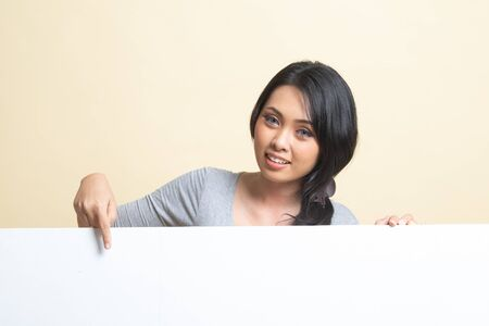 Young Asian woman point to a  blank sign   on beige background 免版税图像