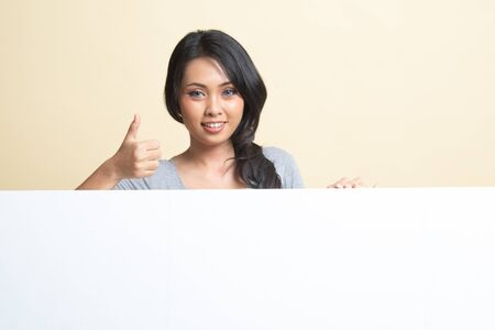 Young Asian woman show thumbs up with blank sign   on beige background 免版税图像