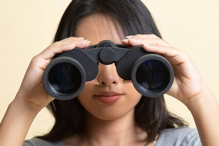 Young Asian woman with binoculars on beige background