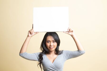 Young Asian woman with white blank sign   on beige background 免版税图像