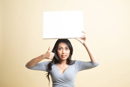 Young Asian woman show thumbs up with white blank sign   on beige background