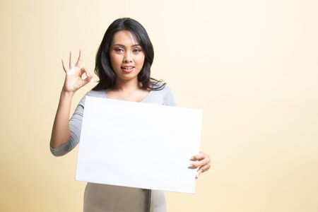 Young Asian woman show OK with white blank sign   on beige background
