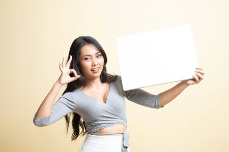 Young Asian woman show OK with  white blank sign   on beige background 免版税图像