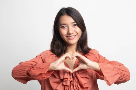 Young Asian woman show heart hand sign on white background Imagens