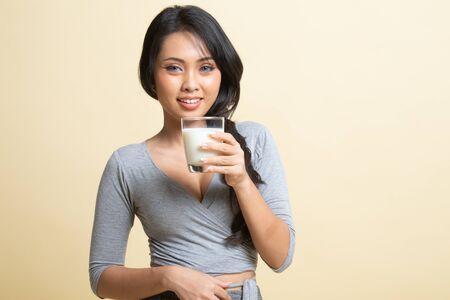 Healthy Asian woman drinking a glass of milk on beige background Foto de archivo
