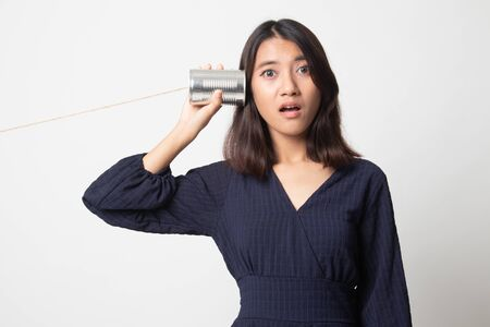 Surprised young Asian woman with tin can phone on white background